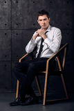 Portrait of successful businessman on a chair. Portrait of strict young businessman in black studio Royalty Free Stock Image