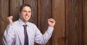 Portrait of successful businessman clenching fists against wooden wall. Digital composite of Portrait of successful businessman clenching fists against wooden Royalty Free Stock Photo