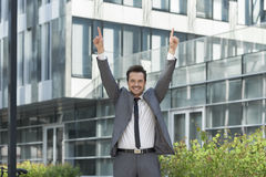 Portrait of successful businessman pointing upwards outside office Stock Image