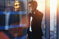 Portrait of successful businessman talking on mobile phone while standing against window in hallway of modern office interior Royalty Free Stock Images