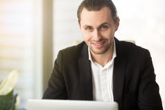 Portrait of successful businessman works on laptop. Portrait of successful businessman works on computer in office. Smiling office worker in front of laptop at Stock Images