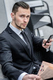 Portrait of a successful businessman. Young man holding a phone Stock Image