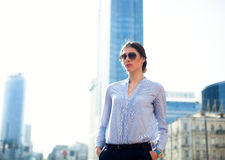 Portrait of successful businesswoman in blue shirt and sunglasses in big city Stock Photography