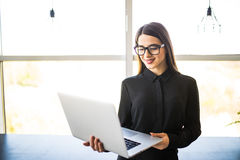 Portrait of successful businesswoman holding laptop in her hands. Happy beautiful confident woman standing at office with notebook. Portrait of successful royalty free stock photography