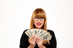 Portrait of successful businesswoman holding money over white background. Royalty Free Stock Photography