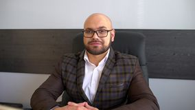 Portrait of Successful Confident Businessman at Office Turning to Camera and Smiling. 4 k. Portrait of successful young businessman in the glasses looking stock footage
