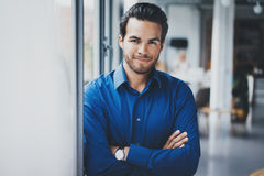 Portrait of successful confident hispanic businessman smiling and standing close from the window in modern office royalty free stock photos