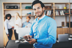 Portrait of successful confident hispanic businessman using tablet in hands and looking at the camera in modern office Royalty Free Stock Images