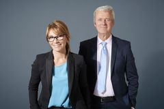 Portrait of a successful financial management standing at isolat. Shot of a middle aged businesswoman and a senior businessman standing together at  background Royalty Free Stock Image