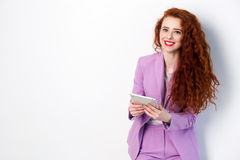 Portrait of successful happy beautiful business woman with red - brown hair and makeup in pink suit holding tablet, looking at cam. Era with toothy smile. studio Stock Image