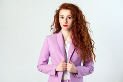 Portrait of successful happy beautiful business woman with red - brown hair and makeup in pink suit. looking at camera with smile. Studio shot on gray Royalty Free Stock Photography