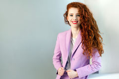 Portrait of successful happy beautiful business woman with red - brown hair and makeup in pink suit.  looking at camera with tooth Stock Photos