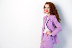Portrait of successful happy beautiful business woman with red - brown hair and makeup in pink suit. looking at camera with toothy. Smile,  studio shot on gray Royalty Free Stock Photography