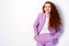 Portrait of successful happy beautiful business woman with red - brown hair and makeup in pink suit. looking at camera with toothy. Smile, studio shot on gray Stock Photography