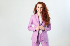 Portrait of successful happy beautiful business woman with red - brown hair and makeup in pink suit. looking at camera with toothy. Smile, studio shot on gray Stock Image