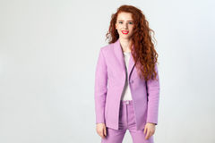 Portrait of successful happy beautiful business woman with red - brown hair and makeup in pink suit. looking at camera with toothy. Smile, studio shot on gray Stock Photos