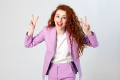 Portrait of successful happy beautiful business woman with red - brown hair and makeup in pink suit showing v sign or peace. Royalty Free Stock Images