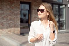 Portrait of a successful happy business woman in a white shirt and sunglasses. Smart watch on a hand stands at the royalty free stock images