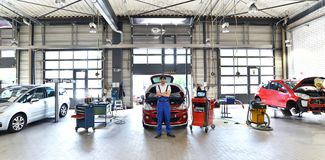 Portrait of a successful mechanic in a garage - repair and servi. Ce of vehicles Stock Photography