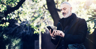 Portrait of successful middle age businessman using modern smartphone while spending time in city park at sunny day Royalty Free Stock Photos