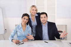 Portrait: successful smiling business team of three people; man. Portrait: successful smiling business team of three people; men and women in the office wearing Royalty Free Stock Photos