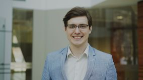 Portrait of successful smiling businessman in glasses looking into camera in modern office. Indoors