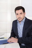 Portrait of a successful young business man at desk. Stock Photo