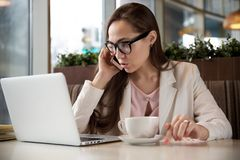 portrait of a successful young business woman with dark hair talking on the phone behind a laptop at a table in stock image