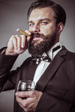 Portrait of a successful young man with retro look holding a gla Royalty Free Stock Photo
