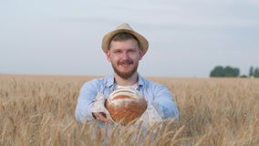 Portrait of sucessful agronomist, young man gives you freshly baked bread and smiles at camera in wheat crop field