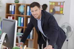 Portrait suited man stood in front computer Royalty Free Stock Photo