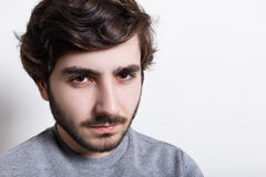 Portrait of sullen angry man with trendy hairstyle and dark beard wearing grey casual sweater looking at camera with serious and s. Evere face expression Royalty Free Stock Photo