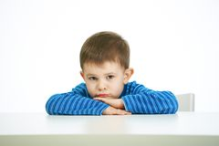 Portrait of sullen little boy sitting at table Royalty Free Stock Photo
