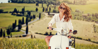 Portrait of summer girl on scooter. Outdoor on Tuscany hiills.Retro shot. Vintage photo Stock Photo