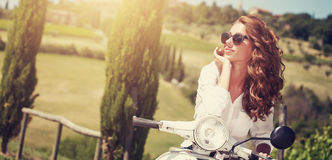 Portrait of summer girl on scooter. Outdoor on Tuscany hiills.Retro shot. Vintage photo Royalty Free Stock Photo