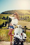 Portrait of summer girl on scooter. Outdoor on Tuscany hiills.Retro shot. Vintage photo Stock Photos