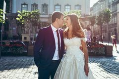 Portrait in the sun. Cheerful adorable newlywed couple is tenderly touching noses in the street. stock images