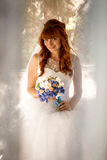 Portrait at sunny day of cute redhead bride holding wedding bouq Royalty Free Stock Image