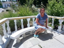 Portrait of a suntanned woman sitting on a bench Stock Photography