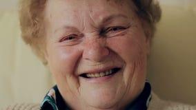 Portrait supérieur, dame âgée heureuse avec des lunettes souriant et regardant l'appareil-photo clips vidéos