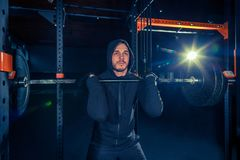 Portrait of super fit muscular young man working out in gym with barbell. On blue Stock Images