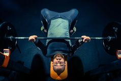 Portrait of super fit muscular young man working out in gym with barbell. On blue Royalty Free Stock Photos