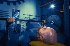 Portrait of super fit muscular young man working out in gym with barbell. On blue Royalty Free Stock Photo