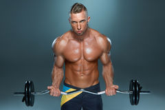 Portrait of super fit muscular young man working. Out in gym with barbell on blue background Stock Images