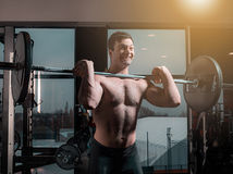 Portrait of super fit muscular young man working out in gym with barbell. On gray Royalty Free Stock Photography