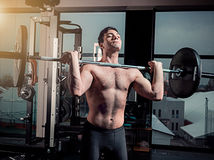Portrait of super fit muscular young man working out in gym with barbell. On gray Stock Photos