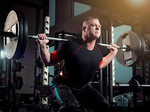 Portrait of super fit muscular young man working out in gym with barbell. On gray Royalty Free Stock Image