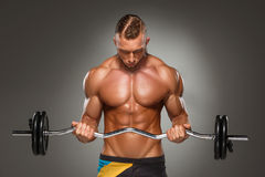 Portrait of super fit muscular young man working. Out in gym with barbell on gray background Stock Photography