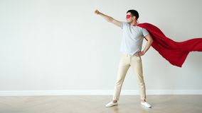 Portrait of super hero in fluttering red cape and mask standing with raised arm. Against empty colorful background. People, character and individuality concept stock video footage