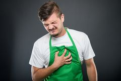 Portrait of supermarket employer holding chest like in pain Stock Photo